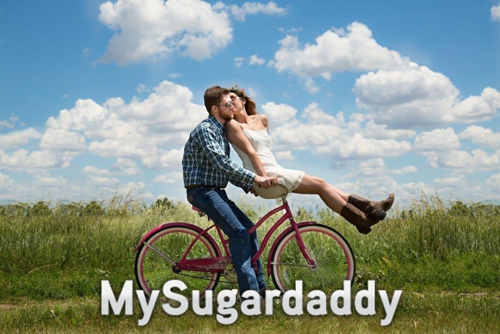 Man sieht ein Pärchen auf einem Fahrrad. Es sieht sehr glücklich aus. Sie fahren durch ein Feld. Die Grundlage zu einer gesunden Beziehung